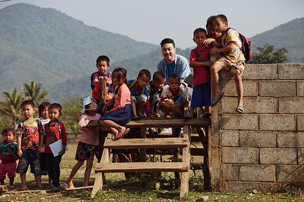 사진작가 전힘찬씨(30·사진 가운데)가 라오스 방비엥의 나몬느아 마을 초등학교에서 아이들과 함께 사진을 찍다 환하게 웃고 있다. 한국 사진작가팀은 사흘 동안 마을 곳곳을 돌며 이동사진관을 열었다.
