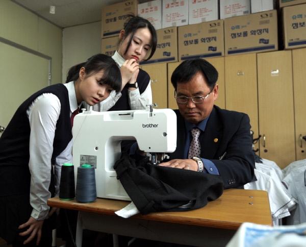 충남 천안쌍용중 김철회 교사가 학교 학생부 상담실에서 재봉틀로 학생들의 교복을 수선하고 있다.      충남도교육청 제공