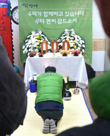 지난 2월 서울 종로구 돈의동 사랑의쉼터에서 열린 마을장례식에 한 쪽방촌 주민이 '나홀로죽음'을 맞은 고인의 영정 앞에서 예를 갖추고 있다.  한겨레두레협동조합 제공