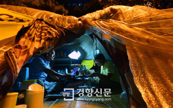 농성장 안 작은 테이블 위에서 각자 작업을 하고 있는 김동애·김영곤 부부 /정지윤 기자