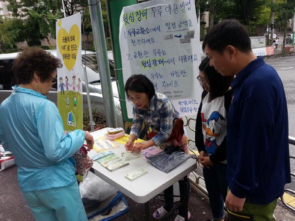 이렇게 '두루' 쓰세요 대전 지역화폐 '두루'를 운영하는 한밭레츠가 두루로만 거래하는 벼룩시장을 찾은 주민에게 법정화폐를 두루로 환전해주면서 이용 방법을 알려주고 있다. 한밭레츠 제공