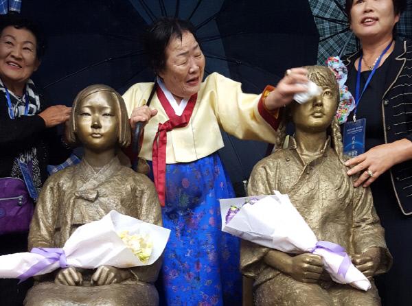 지난해 10월  22일 중국 상하이사범대학에서 열린 한·중 평화의 소녀상 제막식에서 위안부 피해자인 이용수 할머니가  소녀상의 얼굴을 닦아주고 있다. 연합뉴스