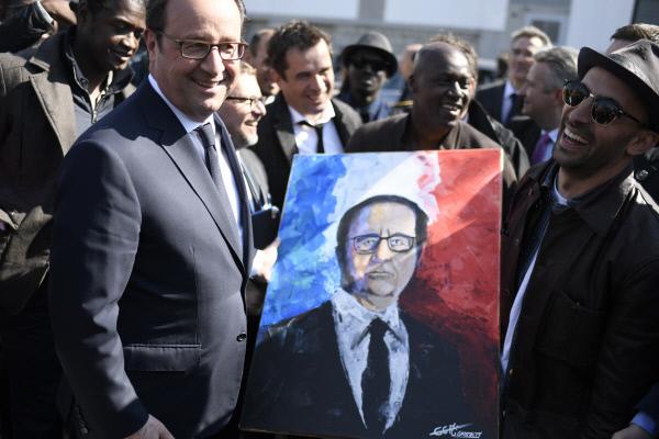 에마뉘엘 마크롱 후보의 '정치적 대부'인 프랑수아 올랑드 프랑스 대통령이 지난 4월19일 파리 동부의 교외 클리시-몽페르메이에서 한 화가가 그린 자신의 초상화를 받고 활짝 웃음을 짓고 있다.  파리/AP연합뉴스
