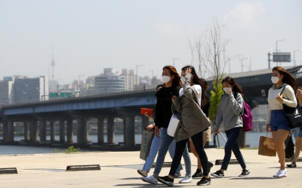 황금연휴 마지막 날이자 중국발 황사로 인한 미세먼지가 전국을 뒤덮은 지난 7일 오전 서울 여의도 한강공원에서 시민들이 마스크를 쓴 채 걷고 있다. 연합뉴스