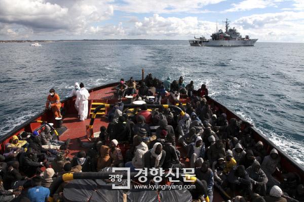 지난달 말 이탈리아 해상에서 구조된 난민들이 1일 포잘로 항구에 닿은 예인선에서 내리기 위해 기다리고 있다. |유엔난민기구(UNHCR)