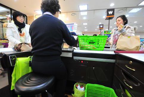 할인점 세이브존에 근무하는 한 직원이 계산대에 앉아 손님에게 영수증을 건네고 있다. 경향신문 자료사진