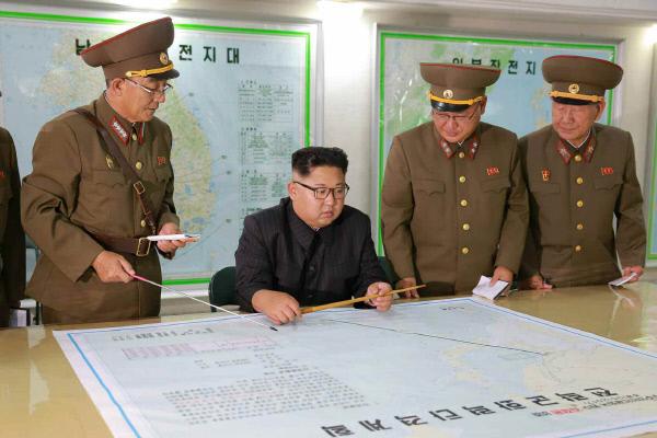 북한의 핵무기와 미사일은 전략군 사령부가 관장한다. 김정은 노동당 위원장이 지난 8월14일 전략군 사령부를 시찰하면서 김락겸 사령관으로부터 '괌 포위사격 방안'에 대한 보고를 받고 있다. 노동신문이 15일 보도한 사진이다.  연합뉴스