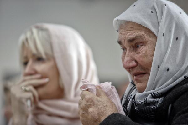 보스니아 주민들이 11월22일 스레브레니차 인근 포토카리에 세워진 학살 추념시설에서 라트코 믈라디치에 대한 ICTY의 판결이 내려지는 장면을 TV로 바라보며 눈물을 흘리고 있다.  AP연합뉴스