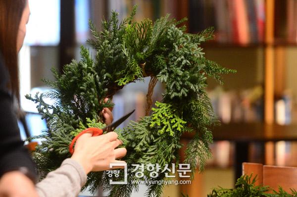 지난 14일 서울 정동 산다미아노 카페에서 진행된 '취미잼잼- 올해는 취미를 갖자' 11월 원데이클래스에 참가한 독자가 삼나무와 측백나무, 향나무를 시계 방향으로 꽂은 리스를 손질하고 있다. 김창길 기자 cut@kyunghyang.com