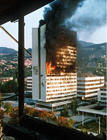 1992년 사라예보 도심의 정부청사가 세르비아계의 포격으로 불타고 있다.  전쟁은 1984년 동계올림픽 주최도시를 석기시대로 돌려놓았다. 위키페디아