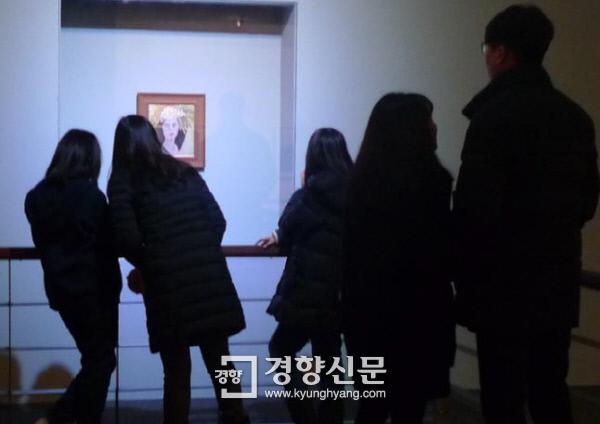 '미인도'를 둘러싼 논쟁은 올해도 미술계 최대 이슈로 꼽힌다. 국립현대미술관은 4월부터 과천관에서 '미인도'를 전시 중이다. 고 천경자 화백 유족은 이 전시에 대해 미술관을 고소했다. 관람객들이 지난 17일 '미인도'를 들여다보고 있다. 김종목 기자 jomo@kyunghyang.com