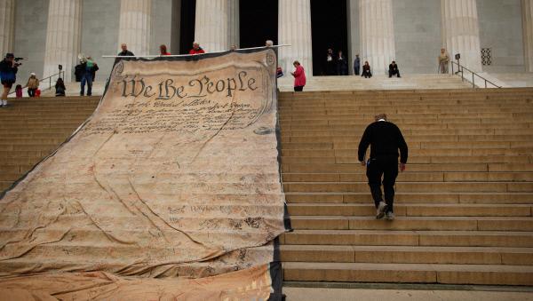 2010년 10월 미국 워싱턴 링컨기념관 앞에서 연방대법원 판결에 항의하는 시위대들이 미국 헌법의 유명한 첫 구절 '위 더 피플(We the People)'이 적힌 대형 펼침막을 설치하고 있다. 미국 정부는 일본 헌법을 만들면서 피플(people)을 인민(人民)으로 번역했다. '위 더 피플'은 백악관 청원 사이트 이름으로도 쓰이고 있다. 당시 연방대법원은 기업과 노동조합의 정치자금 제공을 금지한 선거법을 위헌으로 결정했다.   게티이미지