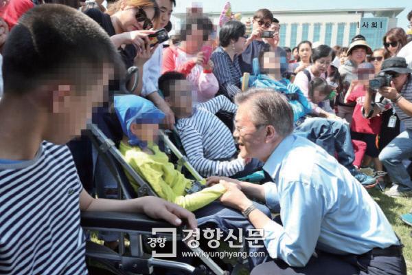문재인 대통령이 대선후보 시절인 지난해 5월 서울 여의도 국회의사당 앞마당에서 열린 행사에 참여한 장애아들과 인사를 나누고 있다. 권호욱 기자