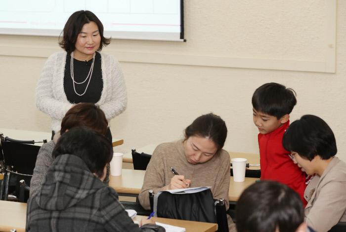 김지혜 코치(맨 왼쪽)가 2월 '인생수업'에 참여한 부모들에게 3분 동안 떠오르는 감정을 25칸 안에 단어로 채워보는 '감정빙고게임'을 시켜보고 있다.  이상훈 선임기자 doolee@kyunghyang.com