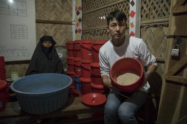 유엔난민기구(UNHCR) 친선대사인 배우 정우성씨가 방글라데시 쿠투팔롱의 난민캠프 내 영상실조센터에서 식량통을 들어보이고 있다. 유엔난민기구 제공