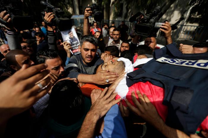 지난 7일(현지시간) 열린 팔레스타인 언론인 야세르 무르타자의 장례식에서 조문객들이 그의 시신에 손을 대며 애도를 표하고 있다.  무르타자는 지난 6일(현지시간) 가자지구 보안장벽 인근에서 팔레스타인 시위대와 이스라엘군의 유혈 충돌을 취재하던 도중 이스라엘군의 총격을 당했고, 다음날인 7일 새벽 결국 사망했다.  가자|AFP연합뉴스