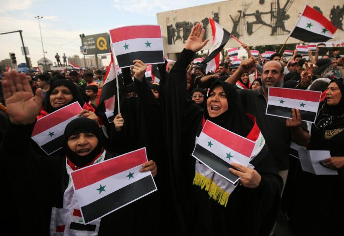 <b>시리아 공습 항의하는 이라크 시민들</b> 이라크 시민들이 15일(현지시간) 수도 바그다드에서 시리아 국기를 흔들며 미국·영국·프랑스 연합군의 시리아 공습에 항의하는 시위를 벌이고 있다. 바그다드 | AFP연합뉴스