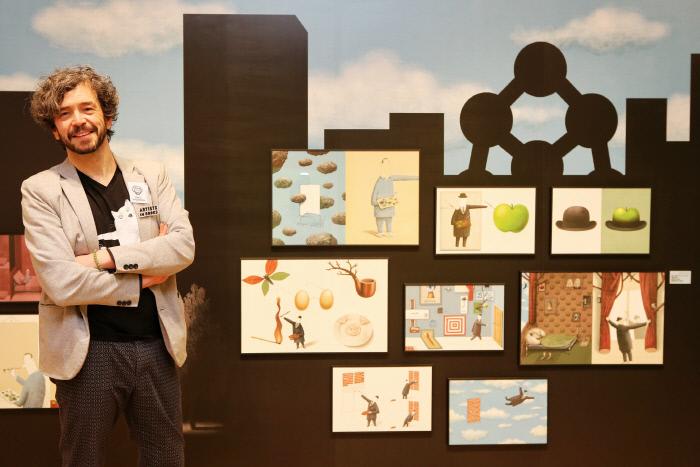 벨기에 그림책 작가 클라스 베르플랑케가 지난 12일 현대어린이책미술관에서 열린 '아티스트 인 북스' 전시장 내에서 자신의 그림들 앞에서 포즈를 취하고 있다. 현대어린이책미술관 제공