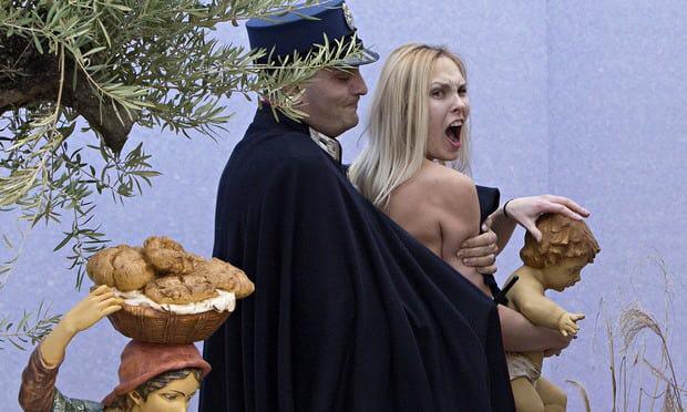 """바티칸의 성베드로 광장에서 상반신을 노출한 채 """"신은 여성이다""""라고 가슴에 쓴 구호를 외치는 페멘 활동가를 바티칸 경찰이 체포하고 있다. 이 활동가는 이틀간 구금됐다가 풀려났다. AP연합뉴스"""