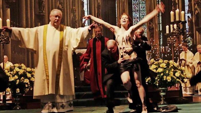 쾰른 대성당에서 열린 성탄미사에 난입한 페멘 활동가를 교회 관계자들이 제지하고 있다.