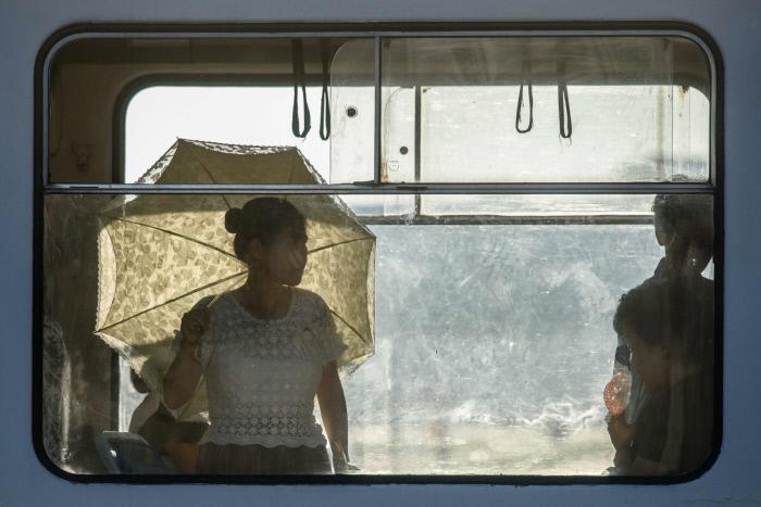 폭염이 이어지고 있는 북한 평양에서 한 시민이 양산을 든 채 전차에 올라있다. / AFP연합뉴스