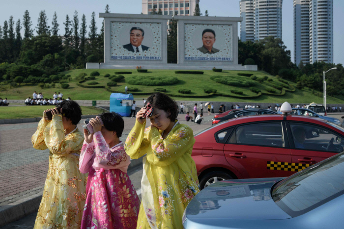 뜨거운 태양으로부터 얼굴을 가린 북한 주민들이 평양거리를 걷고 있다. /AFP연합뉴스