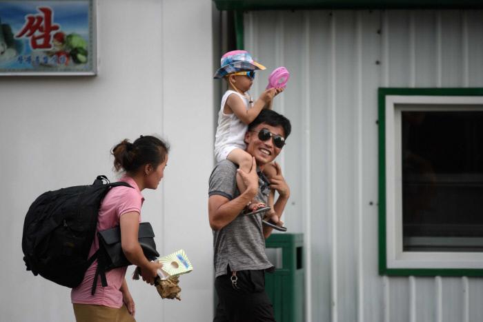 손 선풍기를 든 아이를 무등 태운 아빠가 평양 거리를 걸어가고 있다. /AFP연합뉴스