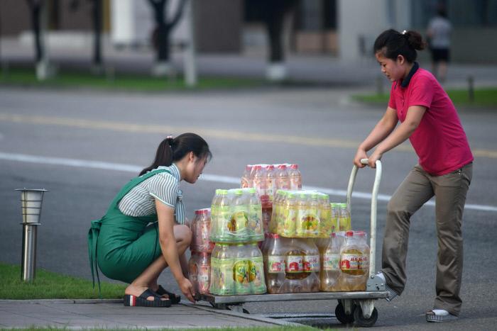 평양 거리에서 여성들이 과일음료를 실은 카트를 끌고 있다. / AFP연합뉴스