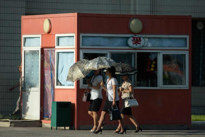 양산을 받쳐든 평양 시민들이 거리를 걷고 있다. / AFP연합뉴스
