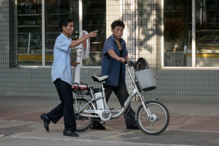 평양 시민들이 자전거에 선풍기를 싣고 거리를 걸어가고 있다. /AFP연합뉴스