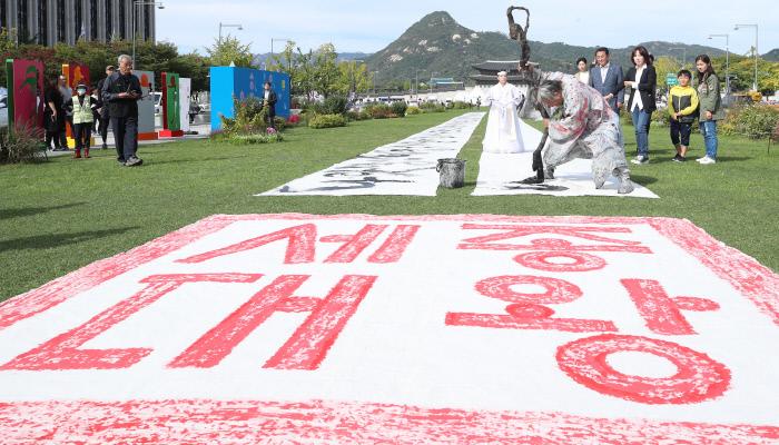 한글날을 하루 앞둔 8일 오후 서울 광화문 광장에서 서예가 쌍산 김동욱 씨가 길이 120m, 폭 1.6m 크기의 광목천에 훈민정음 서문을 쓰는 서예 퍼포먼스를 하고 있다. 연합뉴스