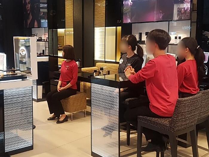 지난 2일 오후 '백화점면세점화장품노조연대' 직원들이 대기 시간에 앉을 수 있는 권리를 알리기 위해 매장에서 '앉기 행동'을 하고 있다. 사진 전국서비스산업노동조합연맹