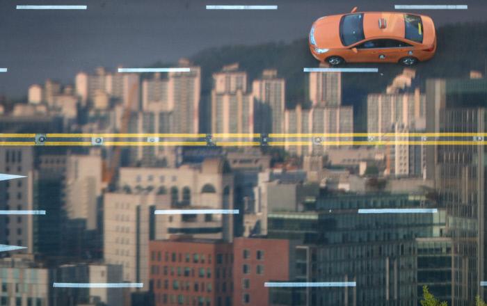 카카오의 카풀앱 서비스에 반대하는 택시 노동자들이 집단행동에 나선 지난 18일 서울 광화문 인근의 한 건물 유리에 도로 위를 달리는 택시 모습이 반사돼 보인다. 연합뉴스