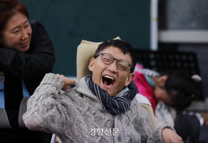안홍경씨(58)가 활동지원사와 얘기하며 웃고 있다. 안씨는 개인전을 연 화가이다. 팔에 붓을 끼워 그림 하나를 완성하는 데 6개월이 걸린다고 했다. /강윤중 기자