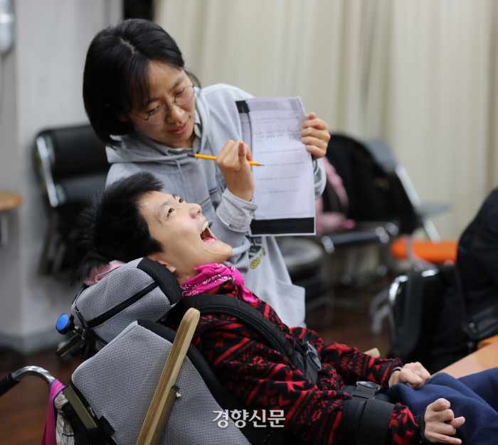 커다란 휠체어에 고정된 정수연씨(37)가 김유미 교사와 수학 문제풀이를 하고 있다. 수연씨는 짧은 외마디 말을 토해내기 위해 온몸의 에너지를 쏟았다. 얼굴에는 금세 땀이 맺혔다.  /강윤중 기자