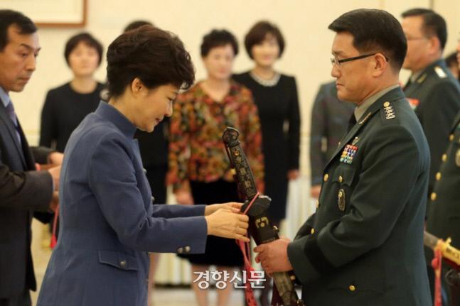 박근혜 전 대통령이 2013년 11월 15일 청와대에서 열린 군 장성 수치 수여식에서 이재수 당시 신임 국군 기무사령관의 삼정도에 수치를 달아주고 있다./연합뉴스