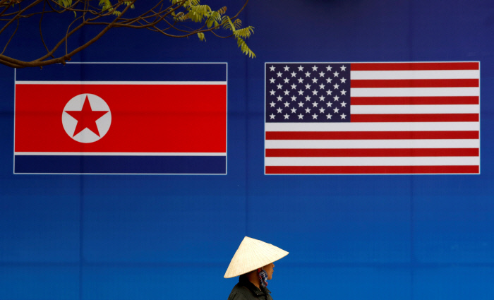 두번째 북·미 회담을 앞두고 지난 2월25일 베트남 하노이 거리에 내걸린 인공기와 성조기 플래카드 밑으로 전통 모자를 쓴 행인이 지나가고 있다.  로이터연합뉴스