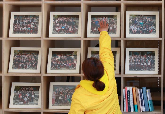<b>닿고 싶은 너</b> 세월호 참사 5주기를 하루 앞둔 15일 유족이 서울 광화문광장 기억·안전 전시공간 '기억과 빛'에 놓인 안산 단원고 학생들의 반별 기념사진을 어루만지고 있다.  연합뉴스
