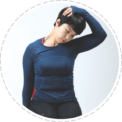 <b>(사진 1)목 스트레칭</b> 의자에 앉아 왼손을 엉덩이 밑에 깔고 오른손으로 왼쪽 머리 뒤통수를 잡아 사선으로 당기듯 떨궈 10초간 유지한다. 반대쪽도 같은 방법으로 운동한다.