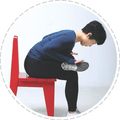 <b>(사진 2)척추·가슴·엉덩이 스트레칭</b> 의자에 앉아 오른발을 왼쪽 무릎 위에 올린 뒤 허리를 펴고 가슴이 다리에 닿는다는 기분으로 내려갈 수 있는 범위까지 앞으로 구부려 10초간 유지한다. 반대쪽도 같은 방법으로 운동한다.