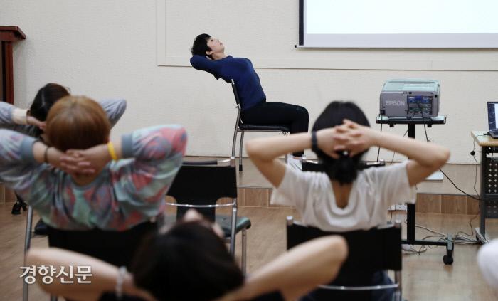 지난 22일 서울 중구 정동 경향신문사 강의실에서 생존운동을 배우려고 모인 참가자들이 임미정 트레이너와 함께 의자를 활용한 스트레칭 동작을 하고 있다. 김정근 선임기자