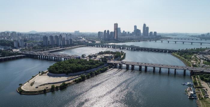화창한 날씨를 보인 지난달 31일 서울 용산구 이촌동 상공에서 드론을 이용해 찍은 한강대교(맨 앞) 위로 파란 하늘이 펼쳐져 있다. 1917년 한강에 인도교로는 처음으로 건설된 한강대교는 1950년 한국전쟁 때 폭파됐다. 한강에 있는 다리 중 최초로 건설되고 동시에 최초로 무너진 다리이기도 하다. 다리 가운데 섬(노들섬)이 있기 때문에 섬 남쪽과 북쪽을 모두 합하면 총길이는 1036m가 된다.