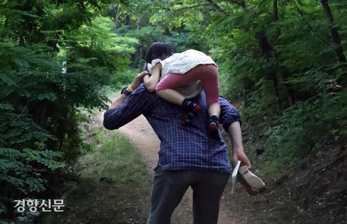 딸 리솔이가 아빠 임종진씨의 등을 타고 어깨 위로 올라가고 있다.