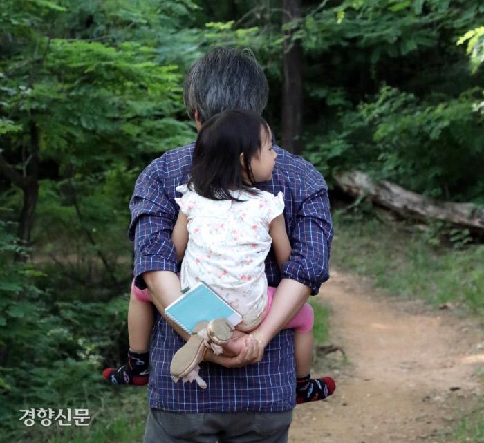 리솔이가 아빠 등에 업혀 산책로를 지나 집으로 향하고 있다.