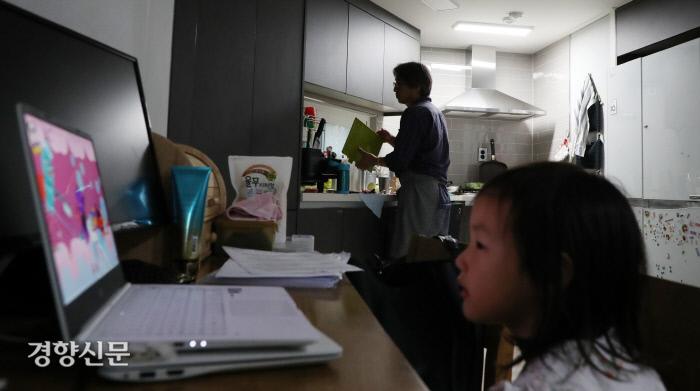 리솔이가 노트북으로 동영상을 보는 동안 임씨가 설거지를 하고 있다.