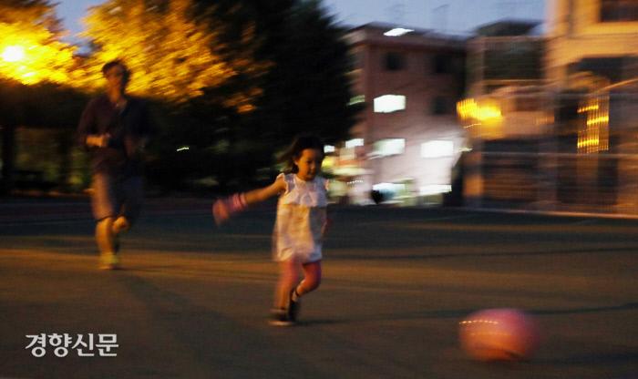 임종진씨와 딸 리솔이가 집 근처의 학교 운동장에서 공놀이를 하고 있다.