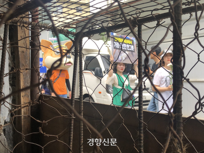 서울과 부산 등지에서 모인 동물보호단체 회원 150여명이 초복인 12일 오후 대구 북구 칠성 개시장에서 시설 폐쇄 등을 촉구하며 행진하고 있다. 회원들이 개를 가뒀던 것으로 보이는 철장을 바라보고 있다.|백경열 기자 merci@kyunghyang.com