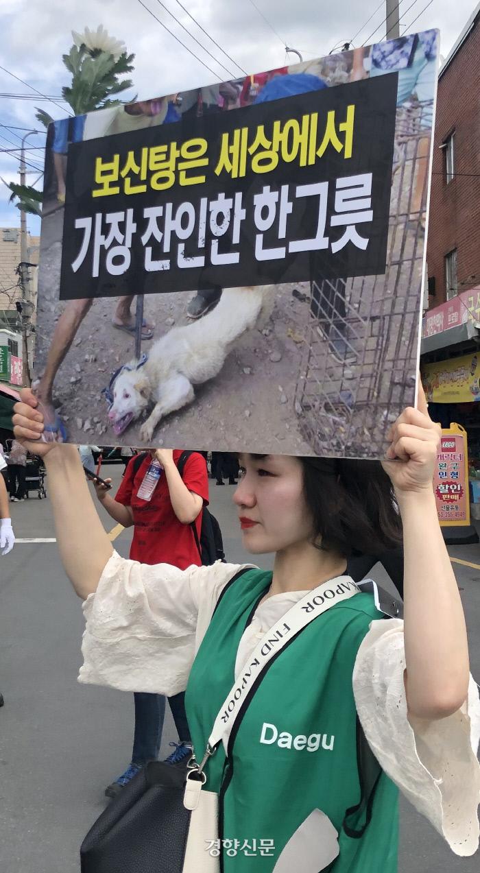 12일 대구 북구 칠성 개시장에서 시설 폐쇄 등을 촉구하며 집회가 열린 가운데, 한 동물보호단체 회원이 '보신탕은 세상에서 가장 잔인한 한그릇'이라고 적힌 펼침막을 든 채 울먹이고 있다.|백경열 기자 merci@kyunghyang.com