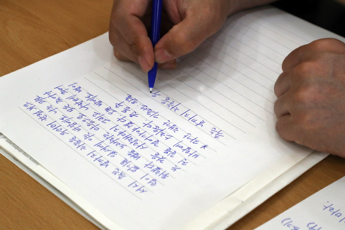 '인생수업 : 글씨 콤플렉스 벗어나는 법' 강연에서 한 참석자가 윤동주 시인의 '서시'를 써 보고 있다.  김정근 선임기자 jeongk@kyunghyang.com