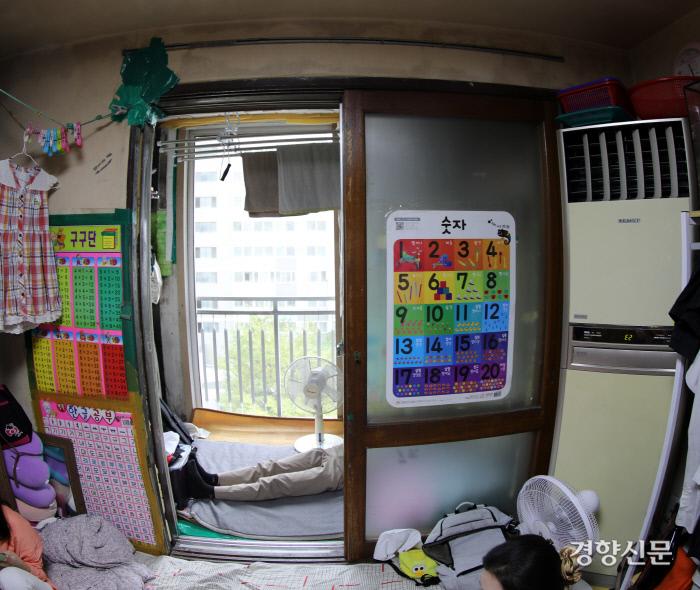 경기도의 한 영구임대아파트에 사는 조승자씨(63)의 집엔 성장기 아이들 5명이 한데 모여 잔다. 세탁기와 빨래걸이, 잡동사니 등이 놓인 베란다가 둘째 현우(15)의 '방'이다.  사진 김창길 기자 cut@kyunghyang.com